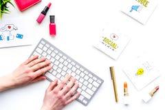 Pracuje biurko piękna blogger z ogólnospołecznymi medialnymi ikonami i kosmetykami na białej tło odgórnego widoku kopii przestrze Obrazy Stock