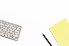 Pracuje biurowego biurko z klawiaturą, żółtym notepad i czarnym p, zdjęcie stock
