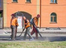 Pracy brygada używa narzędzia dla rozprzestrzeniać asfaltową kruszkę w dziury w drodze Pracownika podmuchowy pył od dziur w r out obrazy stock