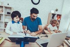 Pracy w domu Laptop Ojca Dwa chłopiec homework zdjęcie stock