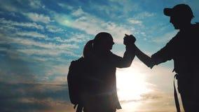 Pracy zespołowej podróży pojęcia styl życia biznesowa wygrana drużynowi turyści mężczyźni i kobieta zmierzchu sylwetki pomoc trzą zbiory