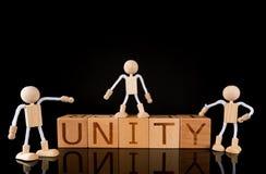 """Pracy zespołowej pojęcie, Drewniany sześcianu blok z słowa """"UNITY† i Drewniane kij postacie, zespalamy się obraz royalty free"""