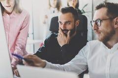 Pracy zespołowej pojęcie Młodzi coworkers dyskutuje nowego biznesowego projekt w nowożytnym biurze Grupa trzy ludzie analizuje ra fotografia stock