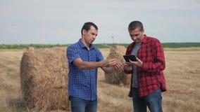 Pracy zespołowej rolnictwa mądrze uprawia ziemię pojęcie dwa mężczyzn rolników pracownika studiuje haystack w polu na cyfrowej pa zdjęcie wideo