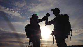 Pracy zespo?owej podr??y poj?cia biznesowa wygrana drużynowi turyści mężczyźni i kobieta zmierzchu sylwetki pomoc trząść ręka suk zbiory wideo