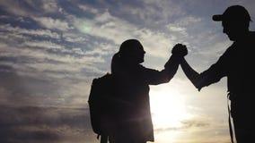 Pracy zespo?owej podr??y poj?cia biznesowa wygrana drużynowi turyści mężczyźni i kobieta zmierzchu sylwetki pomoc trząść ręki zwy zdjęcie wideo