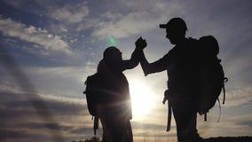 Pracy zespo?owej podr??y poj?cia biznesowa wygrana drużynowi turyści mężczyźni i kobieta zmierzchu sylwetki pomoc trząść ręka suk zdjęcie wideo