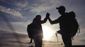 Pracy zespo?owej podr??y poj?cia biznesowa wygrana drużynowi turyści mężczyźni i kobieta zmierzchu sylwetki pomoc trząść ręka suk zbiory