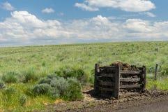 Pradera rural con los posts de la cerca de la roca Imagen de archivo
