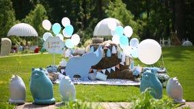 Prado adornado con los baloons, las figuras de animales y las flores metrajes