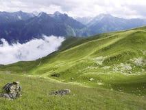 Prado alpestre Sol sobre hierba verde y montañas melancólicas detrás Fotografía de archivo libre de regalías