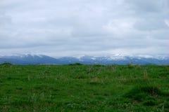 Prado com as montanhas no backgroung Imagens de Stock
