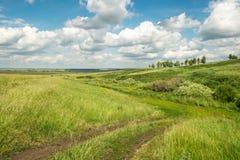 Prado com pista do país e nuvens no céu Foto de Stock