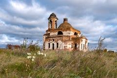 Prado con las flores y el cielo azul en el fondo de la iglesia destruida foto de archivo libre de regalías
