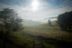 Prado con una pequeña capilla cubierta por el sol y la neblina 2 fotos de archivo