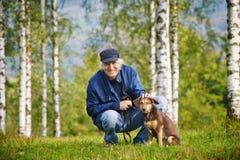 Prado de los árboles del perro del hombre Fotografía de archivo