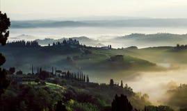 Prado de Toscânia na manhã enevoada Paisagem rural na névoa durante o tempo do nascer do sol e nos montes na província de Itália fotos de stock royalty free