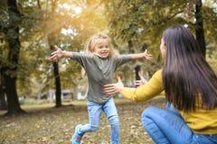 Prado del ion de la madre y de la hija Niña que corre a su mothe Fotos de archivo