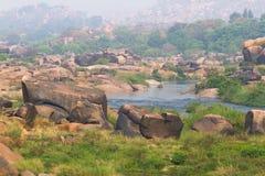 Prado del río de Tungabhadra del pueblo de Hampi Ajardine con agua, palma, roca, piedras La India, Karnataka Fotografía de archivo