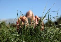 Prado del verano con los pies de la mujer Imagenes de archivo