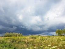 Prado del verano en los rayos del sol con una nube tormentosa inminente Cambio del tiempo Tormenta en un día soleado Naturaleza d fotos de archivo libres de regalías