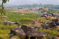 Prado do rio de Tungabhadra da vila de Hampi Ajardine com água, palma, rocha, pedras Índia, Karnataka Fotografia de Stock