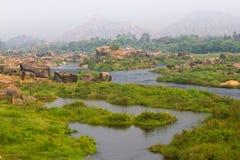 Prado do rio de Tungabhadra da vila de Hampi Ajardine com água, palma, rocha, pedras Índia, Karnataka Foto de Stock Royalty Free