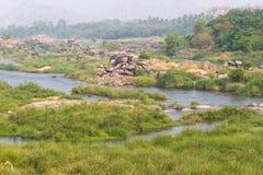 Prado do rio de Tungabhadra da vila de Hampi Ajardine com água, palma, rocha, pedras Índia, Karnataka Imagens de Stock Royalty Free