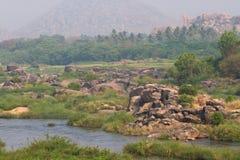 Prado do rio de Tungabhadra da vila de Hampi Ajardine com água, palma, rocha, pedras Índia, Karnataka Fotografia de Stock Royalty Free