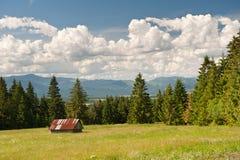 Prado en verano con la pequeña casa blanca, Tatras bajo y el cielo nublado Fotografía de archivo libre de regalías