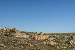 Prado hermoso del valle de la hierba verde con la montaña de la roca en verano de la luz del día con el cielo azul, Matera Italia Imagen de archivo
