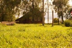 Prado soleado del verano delante de la casa del pueblo Fotos de archivo libres de regalías
