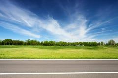 Prado verde con los árboles y la carretera de asfalto Imágenes de archivo libres de regalías
