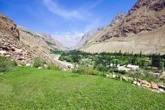 Prado verde de la montaña y río rápido bajo s azul Imagen de archivo