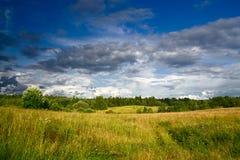 Prado verde sob a paisagem dramática do céu fotos de stock royalty free