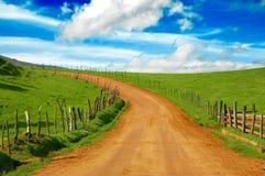 Prado y camino de tierra hermosos Imagenes de archivo