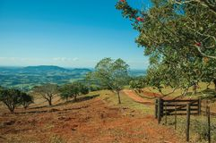 Prados e árvores em um vale verde com porta da exploração agrícola fotografia de stock