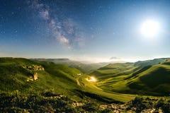 Prados verdes bajo las estrellas y vía láctea Fotos de archivo