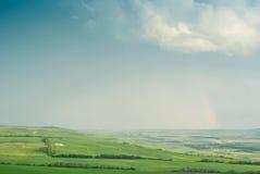 Prados verdes debajo del cielo azul Foto de archivo libre de regalías