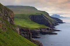 Prados verdes y acantilados gigantes del mar que pasan por alto el océano Imagen de archivo