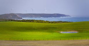 Prados y pastos con las turbinas de viento que se colocan en un acantilado rugoso en el fondo Fotografía de archivo