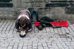 Prag 08 13 2017 Ein obdachloser junger Mann mit einem großen schwarzen Hund auf der Straße Passanten um Geld bitten Lizenzfreies Stockfoto