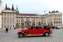 Prag, rotes Retro- Auto der Exkursion der Tschechischen Republik am 26. Dezember 2012 - mit Touristen auf dem Hintergrund Royal P Lizenzfreie Stockbilder