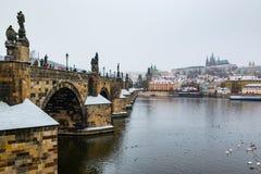 Prag-Schloss und Charles-Brücke am Tag des verschneiten Winters stockbild
