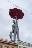 PRAG, TSCHECHE - 12. MÄRZ 2016: Mann, der durch Regenschirm hängt Art Performance in Prag, tschechisch Stockfoto