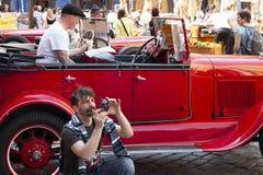 Prag, Tschechische Republik - 20. April 2011: Der Fahrer eines roten Weinleseautos eine Zeitung in Erwartung der Passagiere lesen stockfoto