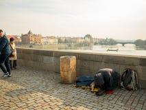 PRAG, TSCHECHISCHE REPUBLIK - 20. FEBRUAR 2018: Kniender Mann und sein Hund, die auf Charles Bridge bitten Bestimmungsort für Rei Stockfotografie