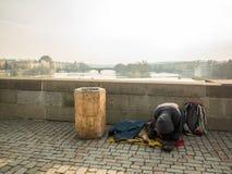 PRAG, TSCHECHISCHE REPUBLIK - 20. FEBRUAR 2018: Kniender Mann und sein Hund, die auf Charles Bridge bitten Bestimmungsort für Rei Lizenzfreie Stockfotografie