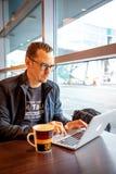 Prag, Tschechische Republik - 01 02 2019: Gut aussehender Mann, der am Tisch sitzt und an dem Laptop im Prag-Flughafencafé arbeit stockfoto