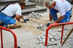 PRAG, TSCHECHISCHE REPUBLIK - 18. JULI 2017: Reparatur des Bürgersteigs Arbeitskräfte, die Pflastersteine des Steins legen Lizenzfreie Stockfotos